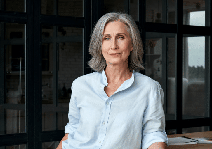 Confident stylish european mature middle aged woman standing at workplace. Stylish older senior businesswoman, 60s gray-haired lady executive leader m@2x
